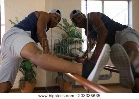 Male dancer stretching leg on barre in dance studio