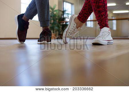 Low section of friends rehearsing dance on wooden floor in studio