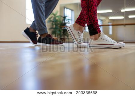 Low section of man with friend rehearsing dance on hardwood floor