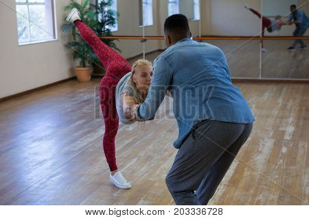 Young friends holding hands while dancing in studio