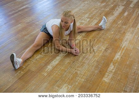 Full length of woman stretching legs on wooden floor in studio