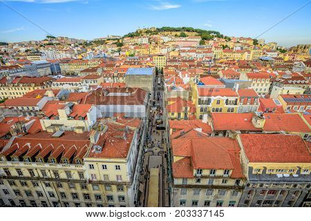 Aerial view of Lisbon downtown and Santa Justa Street to Sao Jorge Castle hill from panoramic platform of Elevador de Santa Justa or Miradouro de Santa Justa connecting Baixa to Igreja do Carmo.