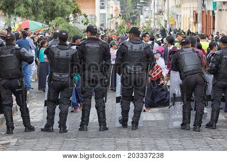 June 29 2017 Cotacachi Ecuador: indigenous quechua people at Inti Raymi summer solstice celebration watched by riot police