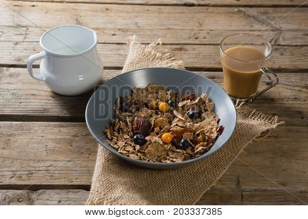Bowl of wheat flakes, blueberry and golden berry with milk jug on table