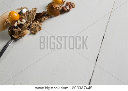 Close-up of wheat flakes and fruit in spoon