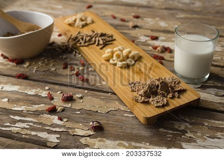Various breakfast cereals and milk on wooden table