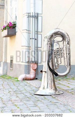 Big shiny base trumpet standing upturned on the street of old town. Outdoors.