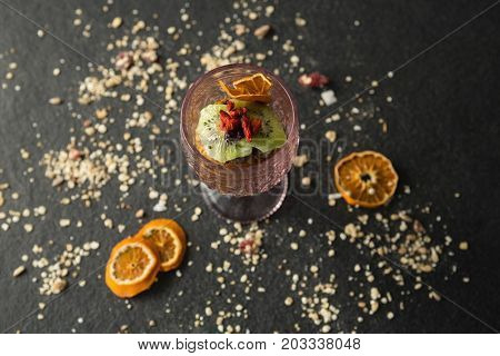 Dried fruits in glass on black background