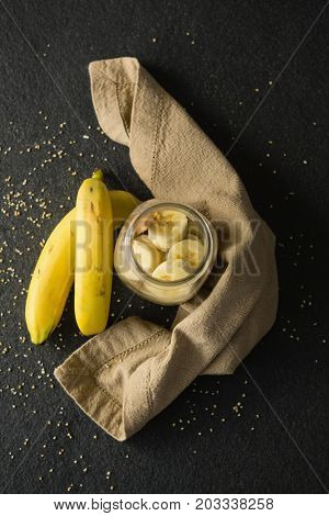 Fruit cereal in jar with napkin cloth on a concrete background