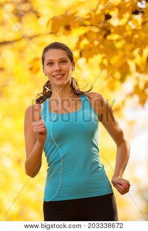 Young brunette woman running in autumn forest, listening to music. Lifestyle and sport photo of healthy style. Outdoor and nature fitness exercise.