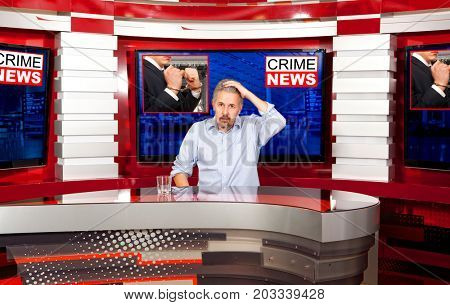 Crime news. A television anchorman at studio during live broadcasting