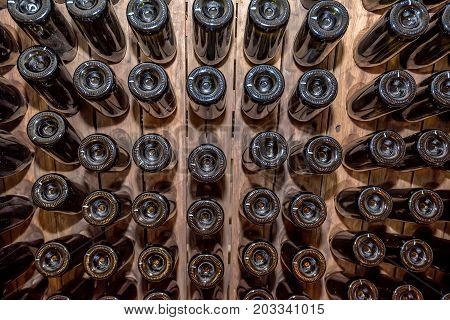 Close up wine bottles aging in wooden stand