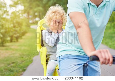 Shot of a little girl looking scare covering her face with her hands sitting in a baby bike seat of a bicycle of her father safety emotions anxiety kids children parenting active lifestyle childhood.