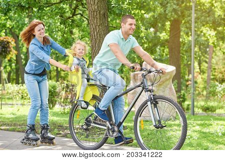 Full length shot of a happy young family enjoying cycling and rollerblading child sitting in a baby bike seat active parents sports lifestyle weekend recreation nature concept.