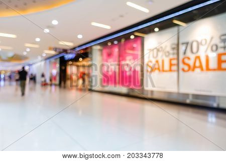 Blurred image of shopping mall and people walking for background usage Sale banner in shop window.