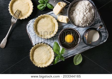Dough for baking quiche tart in small baking form ready for bake. Ingredients above flour, egg, cheese, basil, cream on white wood serving board over black burned wooden background. Flat lay.
