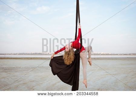 Fit woman in skinny skinny clothes dancing with aerial silk on a sky background, gymnast training on aerial silk