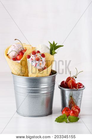 Vanilla ice cream in waffle cones decorated with various berries. Standing in a metal bucket. Sweet cherry in a small metal bucket. On white.