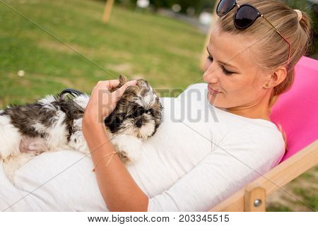 young woman holding a puppy on a sun lounger