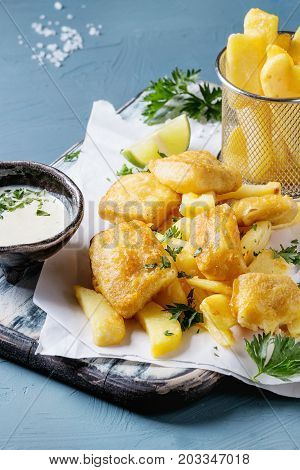 Traditional british fast food fish and chips. Served with white cheese sauce, lime, parsley, french fries in frying basket on white paper over blue concrete background. Close up
