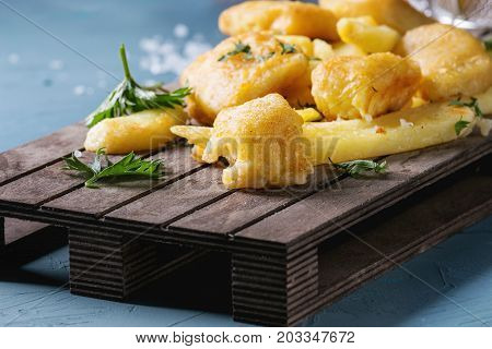 Traditional british fast food fish and chips. Served with lime, parsley, sea salt on wooden serving board over blue concrete background. Close up.