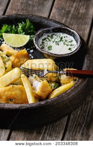 Traditional british fast food fish and chips. Served with white cheese sauce, lime, parsley, fork in terracotta tray over old wooden plank background. Close up