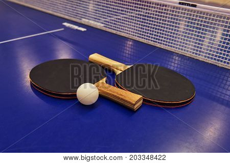 Table tennis racket with a ball on a blue table.