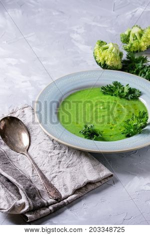 Vegetarian vegan broccoli cream soup served in blue plate with fresh parsley, broccoli, spoon, textile napkin over gray concrete background. Healthy eating.