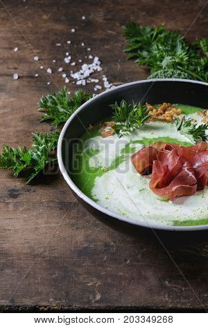 Vegetable broccoli cream soup served in black bowl with italian bresaola ham cream, fried onion, fresh parsley and broccoli over old wooden background. Close up. Healthy eating.