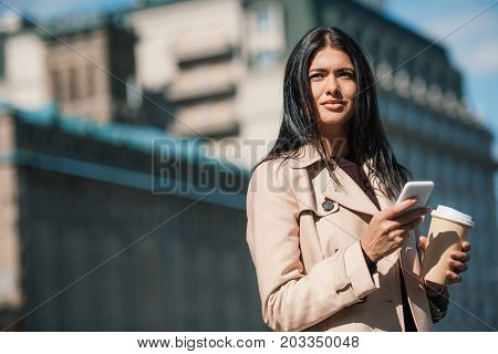Woman In Trench Coat With Smartphone
