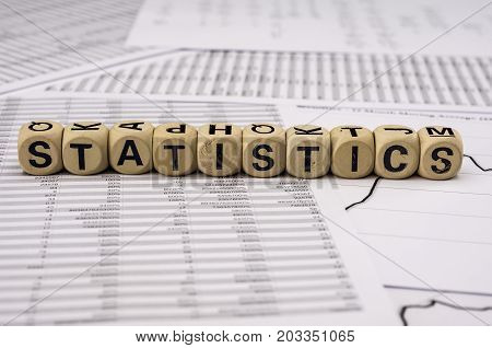 Statistical Analysis Sheets With The Word Statistics Assembled With Wooden Letter Blocks