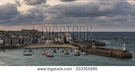 Saint Ives England - April 29 2017: Evening in the harbor city and church with beach of Saint Ives in Cornwall England.