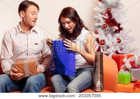 a young couple is sitting on the couch and exchanging christmas gifts.
