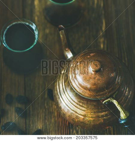 Oriental Middle Eastern vintage copper hummered tea pot, black tea in traditional tulip glasses and black raisins over rustic wooden background, selective focus, square crop