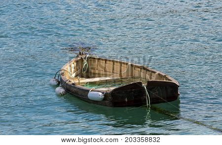 Cornish rowing boat almost sunk in the harbor of Saint Ives Cornwall England.