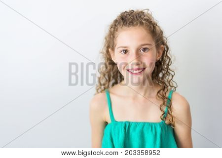 A Portrait of happy, smiling, confident 9 years old girl with curly hair, isolated on gray
