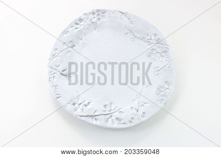 Hand made white plate with the imprint of twigs and berries, isolated on white, horizontal view