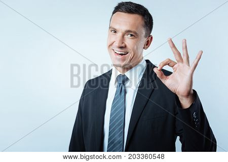Successful businessman. Nice positive joyful man showing OK gesture and feeling happy while being a successful businessman