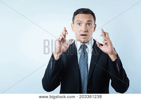Superstitious person. Nice good looking pleasant man looking at you and crossing his fingers while believing in superstitions