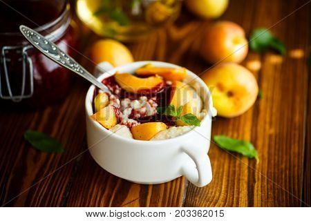 Oatmeal with jam and fresh apricots on a wooden table