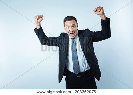 I am happy. Cheerful delighted nice man holding his arms up and showing his happiness while having a successful deal