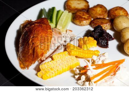 Healthy chicken dinner. Nutritional low calorie slimmer meal. Diet cooking with roast chicken sweetcorn coleslaw potatoes cranberry sauce and cucumber.
