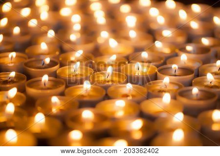 Soft dreamy image of bright candlelight from burning tea light candles. Christmas background image. The romantic glow of yellow flames.