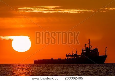 Tropical sunrise or sunset at sea. Calm ocean image of a ship on the horizon. Travel destination and tourism scene.