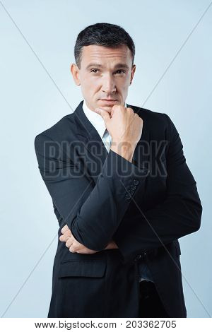 Thoughtful look. Nice pleasant thoughtful man holding his chin while thinking about his work while being a successful businessman
