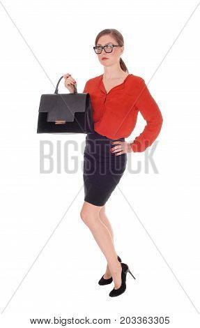 A gorgeous young business woman standing in a red blouse and black skirt holding her black purse with glasses isolated for white background