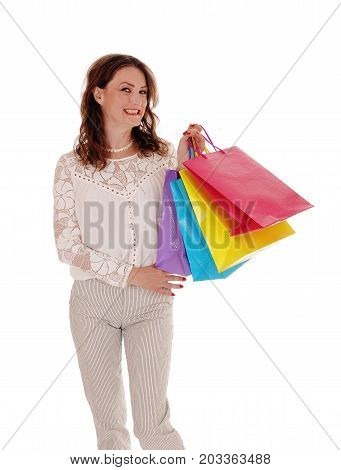 A beautiful young woman in a lace blouse standing isolated for white background holding her shopping bags and smiling