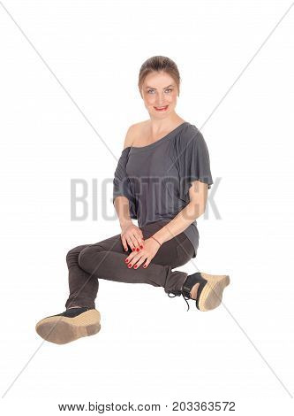 A beautiful young woman in jeans and heels with brunette hair sitting on the floor isolated for white background