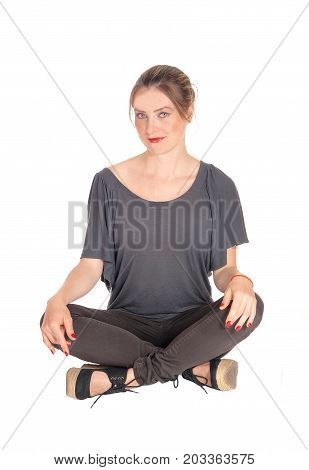 A beautiful young woman in jeans and brunette hair sitting with her legs crossed on the floor isolated for white background.
