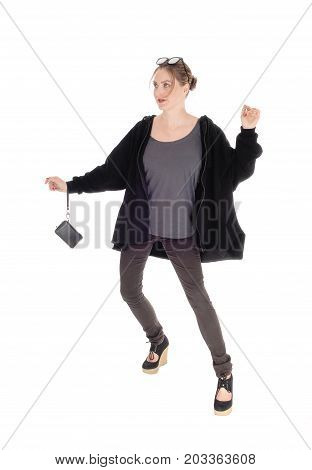 A slim young woman in a black jacket and a small purse ready for a walk with sunglasses on her hair isolated for white background
